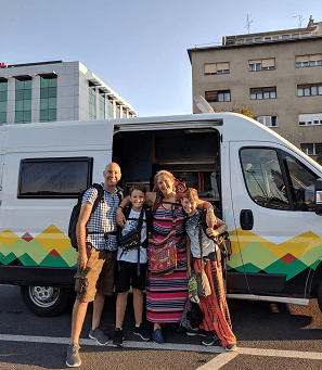Family taking a picture infront of a campervan