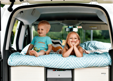 Kids laying in bed inside a campervan