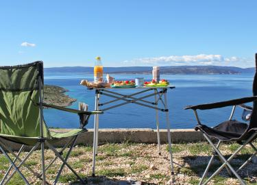 Camping table and chairs besides the beach