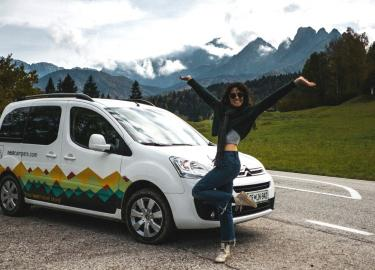Traveler taking picture beside her campervan