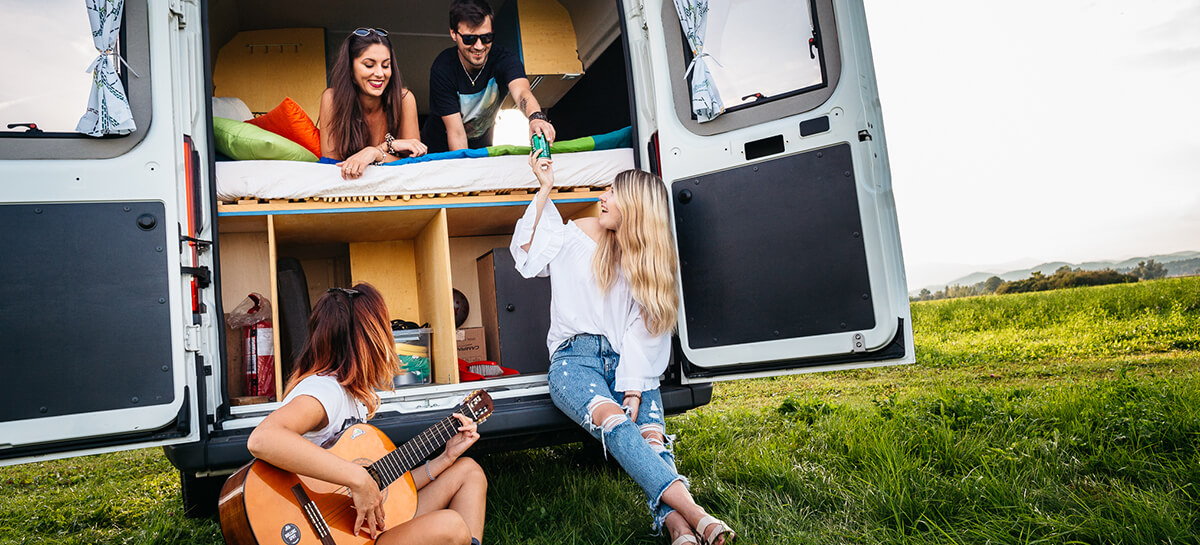 Firends hanging out beside a campervan